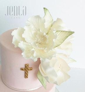 An elegant christening or baptism cake with hand painted script and beautiful suagr flowers in the lightest shade of pink