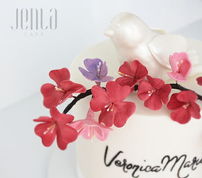Matching cakes for sisters adorned with cherry blossoms and a pair of sugar doves perched atop