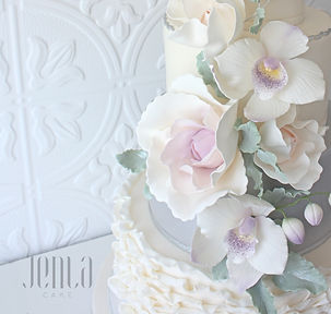 This beautiful wedding cake features stylized frills and ruffling, silver accents and a gorgeous cascade of sugar flowers including roses and orchids in shades of purple and lavender, and dusty miller foliage - JENLA Cake, Toronto