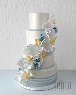 The pearl lustre finish of this wedding cke provides the perfect backdrop for a cascade of white sugar flower with pops of yellow and blue. Silver stripes add clean sophistication.