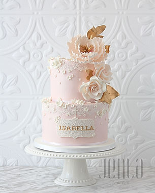 Perfect for a christening or baptism, this pink cake features edible lace, sugar flowers and touches gold.