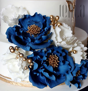 This wedding cake features intricate gold filigree providing the perfect backdrop for luscious navy blue sugar peonies  - JENLA Cake, Toronto