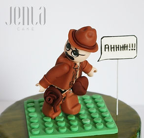 How do you combine 3 different themes intoone cake? You don't, you create 3 different cakes that have a common theme. Knitting cake with yarn is about to roll over Lego Indiana Jones (with some Settlers of Catan in there) while a rugby player tries to shout a warning!