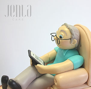 Fondant figurine of a lucky dad sitting in a comfy chair reading his book. Does anyone's parents wear their glasses like this too?
