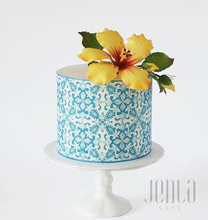 A beautiful blue tile pattern and a hibiscus sugar flower bring a touch of the tropics to this birthday cake