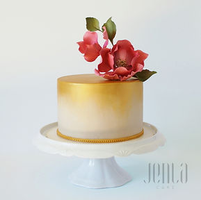 A gorgeous birthday cake with ombre gold fondant and a beautiful sugar flower arrangement