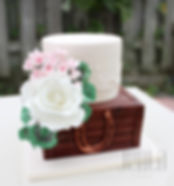 A copper touched horseshoe adorns this rustic cake with fine hand piped details and elegant sugar flowers.