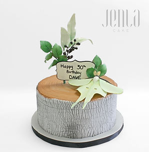 Perfect for a rustic birthda, this cake looks like a tree stump and is decorated with foliage and a luna moth made from gumpaste