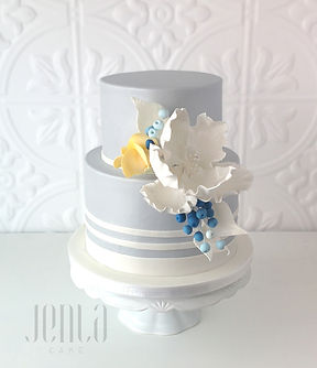 Sophisticated stripes, this elegant grey and white cake features pops of colour from yellow sugar roses and blueberries