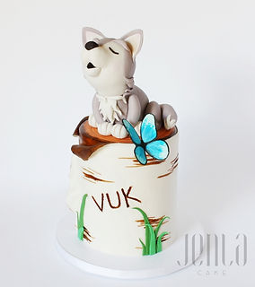 Super cute wolf cub sits perched atop a birch stump, all carved from cake.