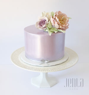 A gorgeous birthday cake with a lavender lustre finish and a beautiful sugar flower arrangement