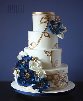 This wedding cake features intricate gold filigree providing the perfect backdrop for luscious navy blue sugar peonies