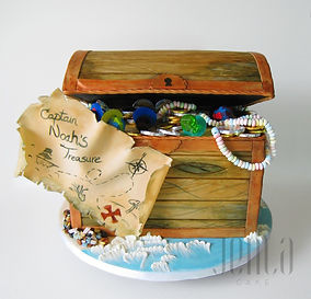 A treasure chest cake complete with fondant wood grain, painted treasure map, and full of real candy and chocolates for all the kids to enjoy!