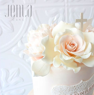 An edible lace name plaque and suagr flowers in the softest shade of pink adorn this christening cake.