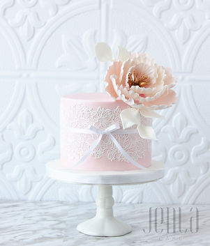 This perfect pink mini cake feautres edible lace and showcases a stunning sugar peonie with gold