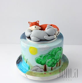 Fondant wolf and fox sleep atop a painted nature scene on this adorable cake