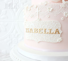 Perfect for a christening or baptism, this pink cake features a name plaque with edible lace and luxurious gold lettering.