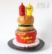 A BBQ themed cake perfect for a bridal shower with ketchup, mustard and hamburger all made of cake!