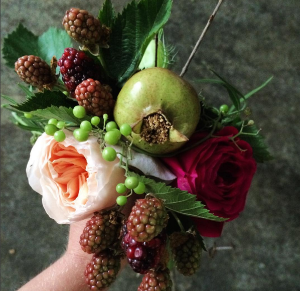 Arrangement with pomegranates and blackberries.