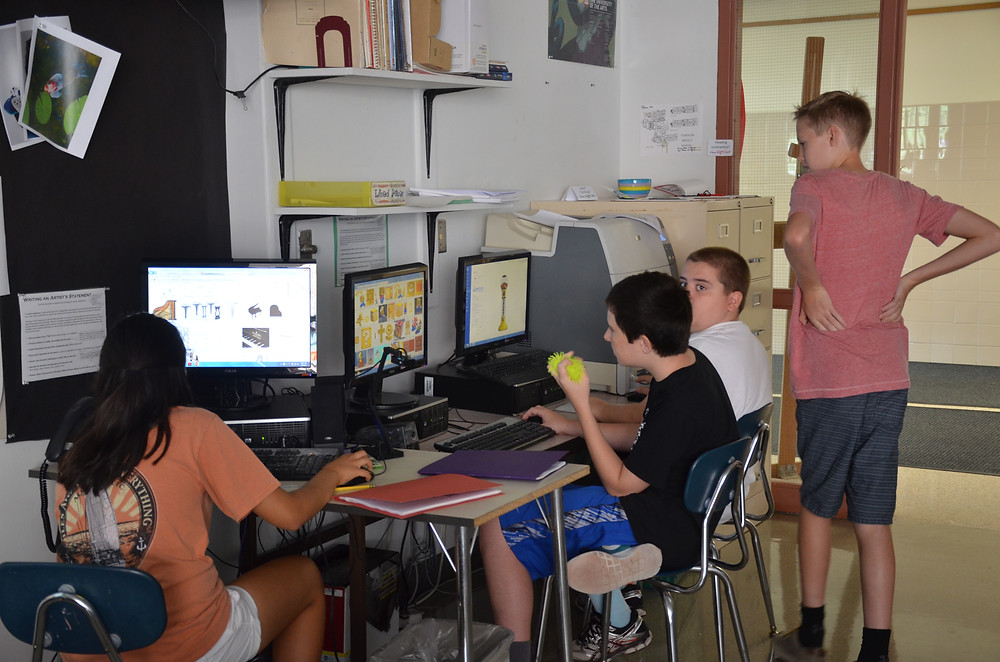 "Using a yellow ""fidgety"" device, the student in the middle has shown he can advocate for his individual learning needs"