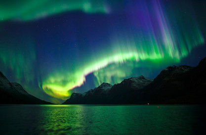 Spectacular display of northern lights near Tromsø, Norway. Taken on a northern lights tour with The Green Adventure. Aurora dancing over a fjord (Ersfjorden). Northern lights reflecting in a fjord.