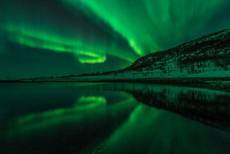 Reflections of northern lights in a fjord near Tromsø, Norway. Taken on a northern lights tour with The Green Adventure.