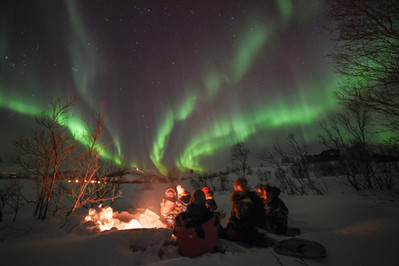 Aurora chasers watching the northern lights by a campfire near Tromsø, Norway.
