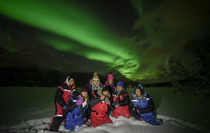 Guests on a northern lights tour, posing for aurora portrait, near Tromsø, Norway. Northern lights tour from Tromsø .