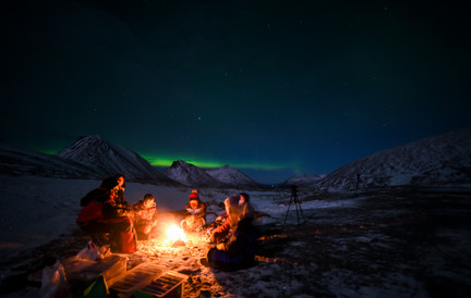 Guests on a northern lights chase sitting by a campfire, near Tromsø, Norway. Northern lights tour from Tromsø .