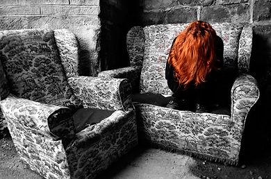 Femme rousse recrovillée sur un canapé