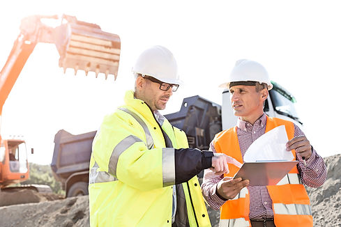 Engineers discussing over documents at construction site.jpg