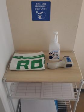 入り口脇に消毒液と検温器を設置しています。