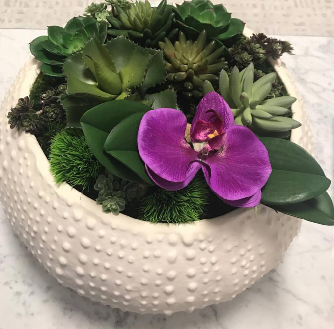 faux flowers in an urchin pot