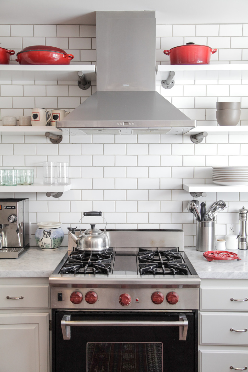 Floating shelves, subway tile, vintage stove, Le Creuset.Kitchen remodel by Lilly Walton Design