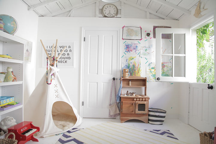 This was a dingy office room turned kids' playroom. We opened up the ceiling, added a charming dutch door, and gave everything a fresh coat of white paint.  Photography by Kate Danson