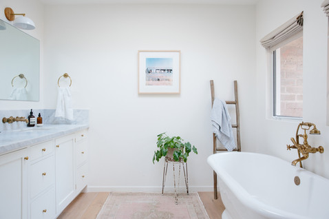Master bath brass fixtures, vintage rug, marble countertops, white cabinets by Lilly Walton Design in Ojai, Ca