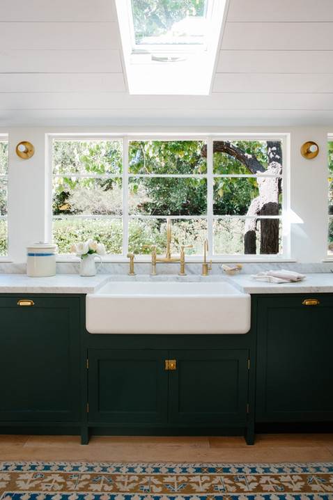 Dark cabinets, vintage rug, and brass fixtures in Ojai, Ca home designed by Lilly Walton Design
