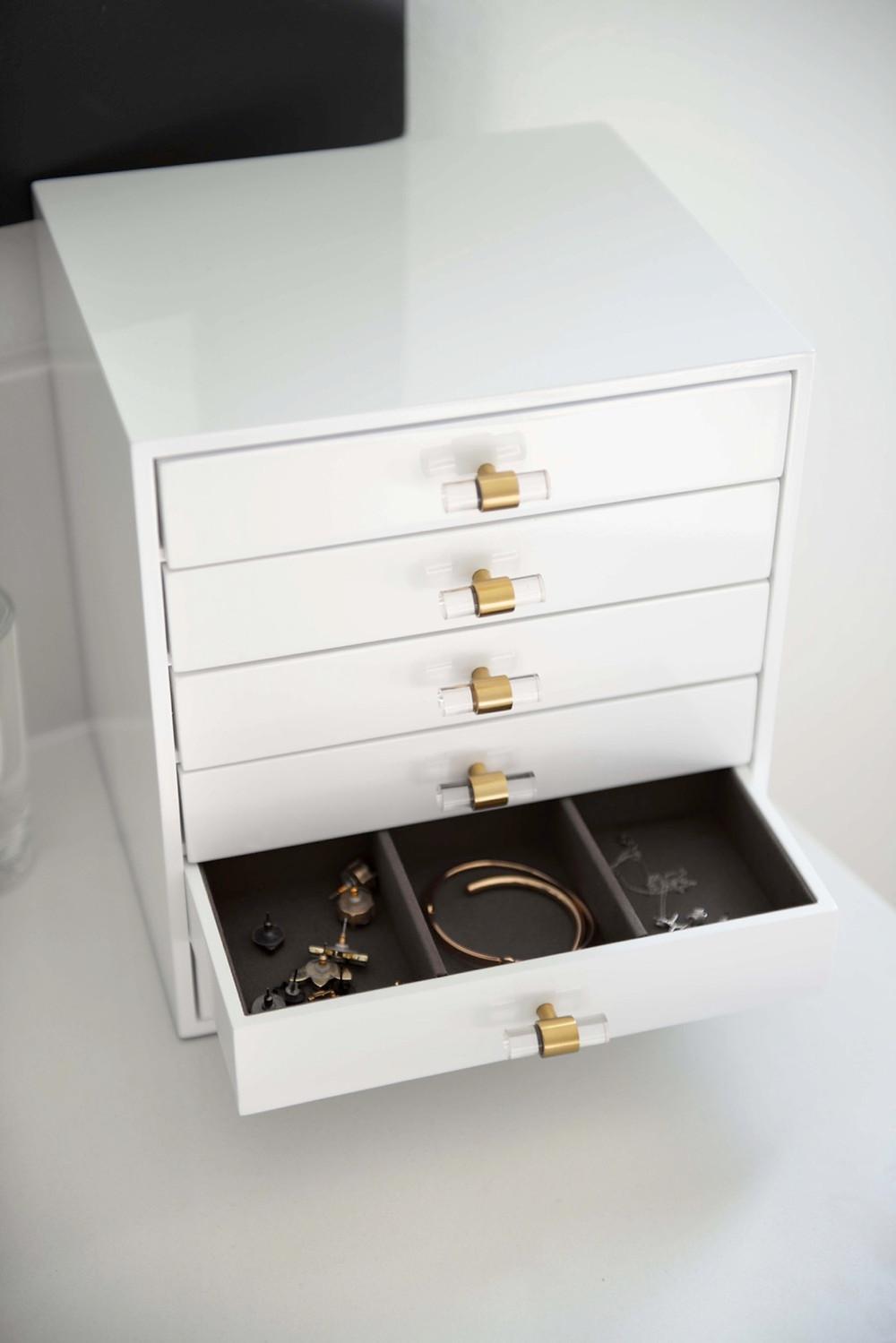 Kendra Scott jewelry box sitting on a luxury bathroom