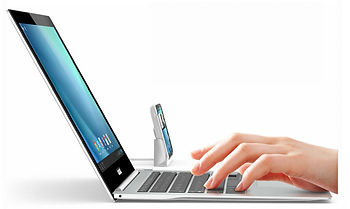 Hand typing at laptop keyboard next to webcam