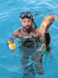 Freediving crew member Sacit catches fresh lobster for dinner at Sailing Chef