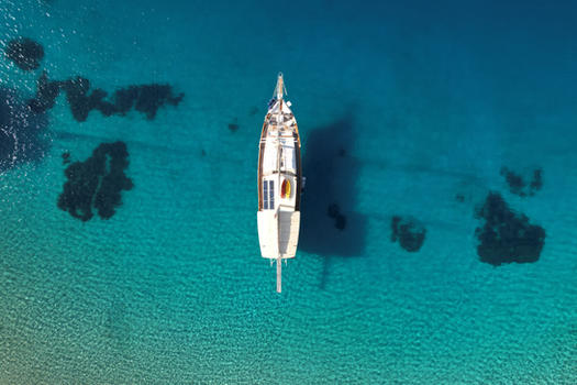 Sailing Chef Gulet seen from above in crustal clear Mediterranean water