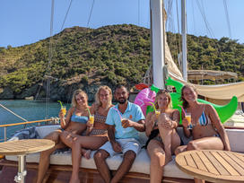 Guests enjoying a cocktail and taking a picture with crew member Sacit