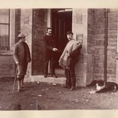 1165 3 men and dog outside house