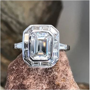 A picture of a white gold ring, bezel set with a Emerald cut diamond