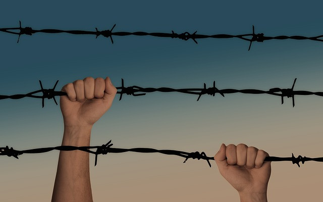 picture of hands climbing on barbed wire. Courtesy of pixabay.com.
