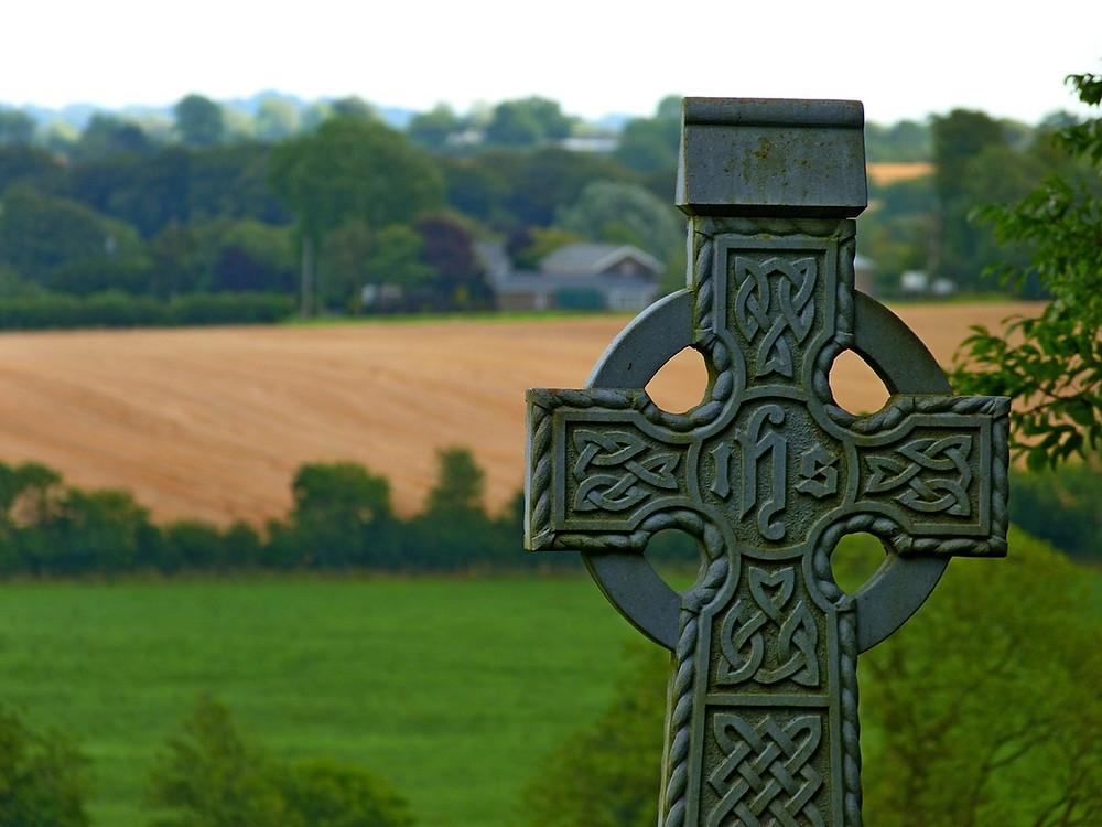 An Irish cross overlooking farmland. Courtesy of www.pixabay.com.