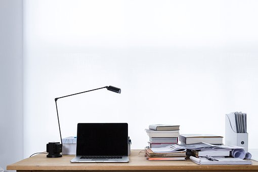 Desk with laptop books and files image