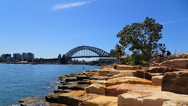 Picture of Sydney Harbour and the bridge in the distance across the rocks. Courtesy of www.pixabay.com