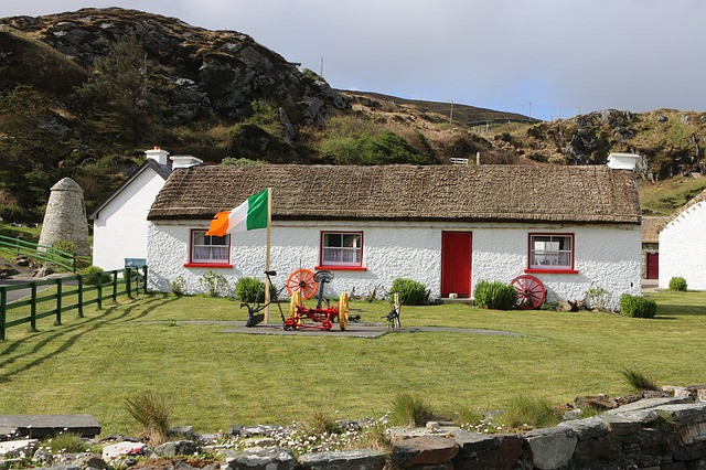 Picture of an Irish cottage with a flag in the front yard. Courtesy of Pixabay.com.