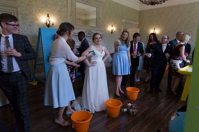 bride and bridesmaids laughing as they play garden games and giant games at wedding